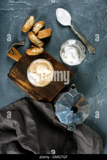 Glasses of coffee with ice cream on rustic wooden board, steel Italian Moka pot over grey concrete textured background - Stock Image