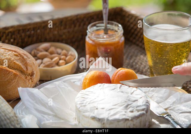 camembert cheese being cut, with apricots, apricot chutney, almonds and beer, set on woven tray - Stock Image