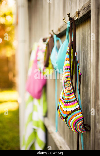 Swimwear hanging off the fence to dry - Stock Image