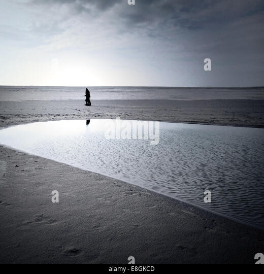 Scenic seascape with people walking on beach - Stock Image