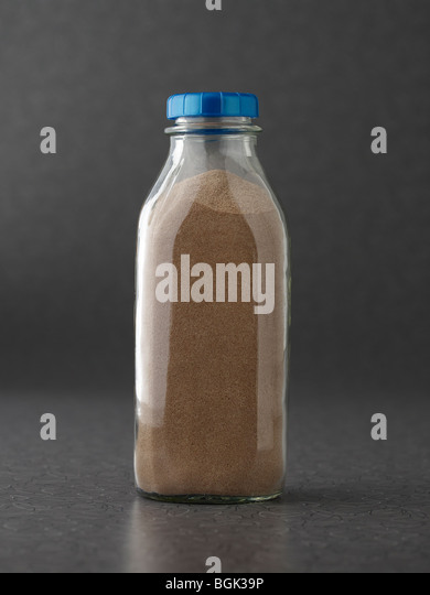 Chocolate milk protein powder in milk bottle on gray surface - Stock Image