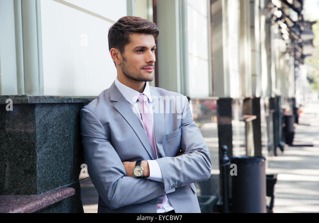 Portrait of a pensive businessman with arms folded standing outdoors in the city - Stock Image