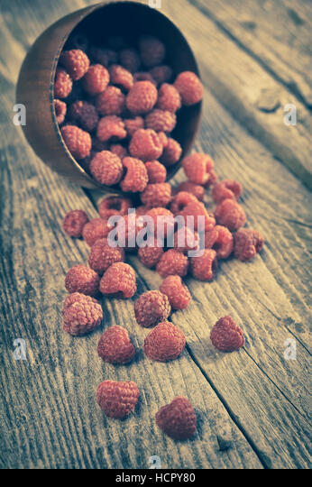 Raspberries in a basket on rustic wooden background - Stock Image