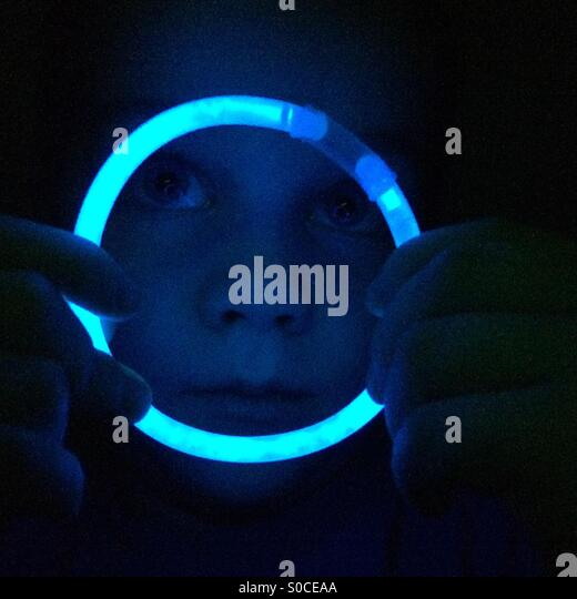 Boy looking through blue glow stick hoop - Stock Image