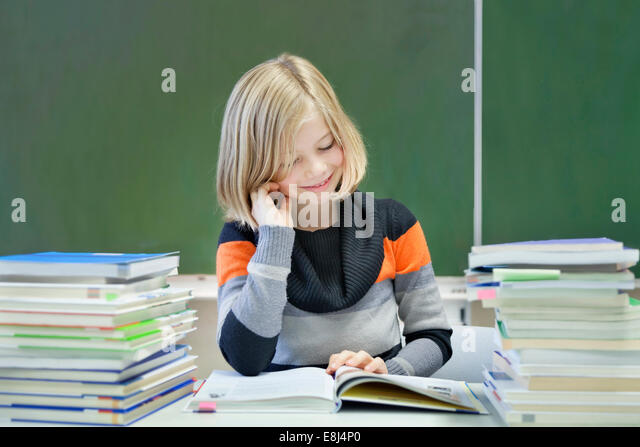 Schoolgirl, 9 years, reading a book whilst sitting between two stacks of books, in front of a blackboard - Stock Image