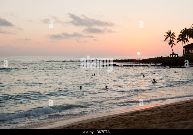 People in sea at sunset - Stock Image