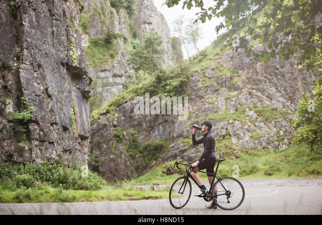 A young cyclist drinking from his bottle in Cheddar George - Stock-Bilder