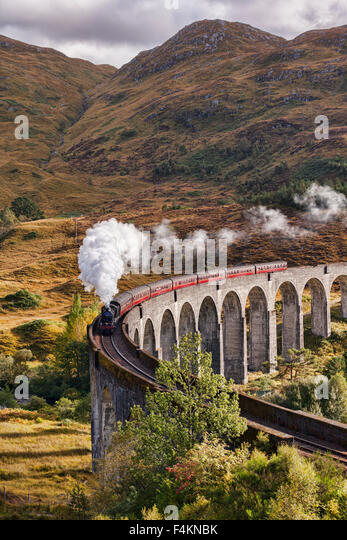 The Jacobite steam train blows steam from the exhaust as it crosses the Glenfinnan Viaduct, Highland, Scotland, - Stock Image
