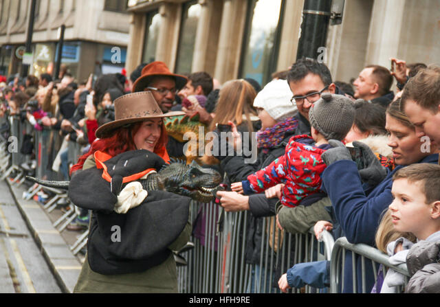 London, UK. 1st January 2017. A performer holding a robotic dinosour interacts with the crowd during the New Year's - Stock Image