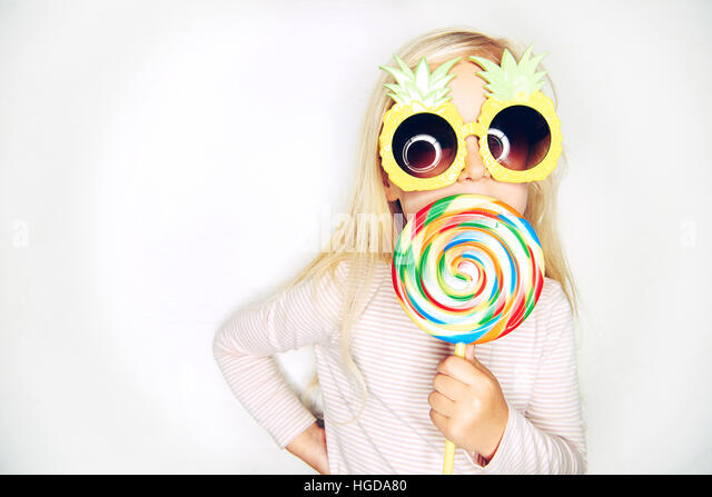 Little girl in creative pineapple sunglasses licking big lollipop and looking at camera on studio white background. - Stock Image