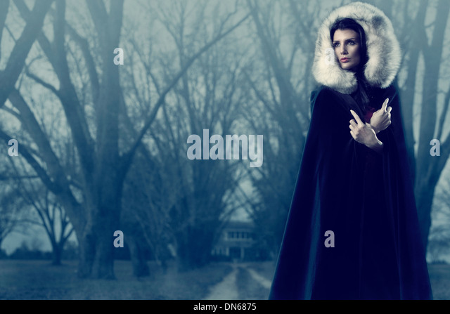 Woman with fur hood and black cape outside on path of trees in the fog - Stock-Bilder
