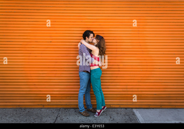 Romantic couple kissing in front of orange shutter - Stock-Bilder
