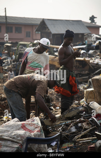 Men looking for useful waste in Olusosum dump site in Lagos.  Recycling is done by human scavengers rummaging the - Stock Image
