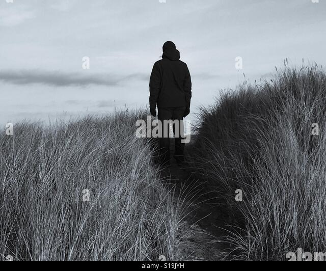 Silhouette of a man standing on a track in sand dunes. - Stock-Bilder