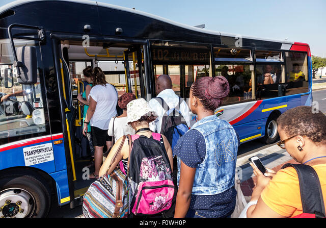 South Africa African Cape Town MyCiTi bus stop riders passengers boarding public transportation Black woman - Stock Image
