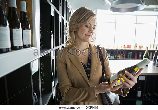 Woman reading label on bottle in wine store - Stock Image