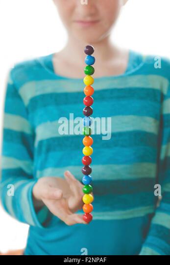 Caucasian girl balancing rainbow candies on finger - Stock-Bilder