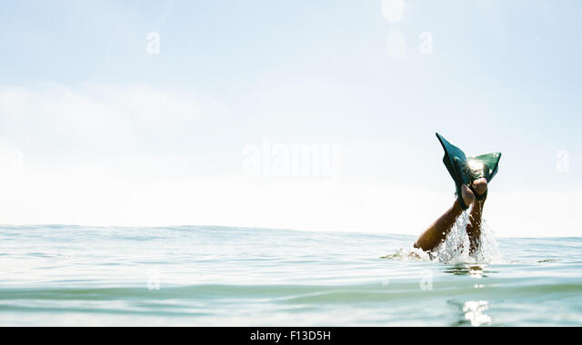 Human legs with flippers sticking out of the sea - Stock Image