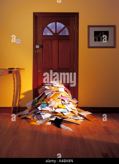Home front door with a pile of junk mail - Stock Image