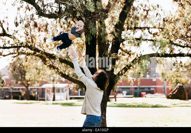 Father throwing son in air - Stock Image