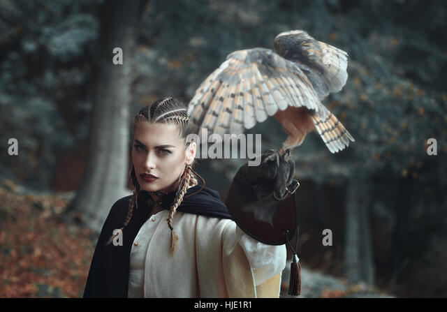 Beautiful lady in surreal forest with an owl . Fantasy and falconry - Stock-Bilder