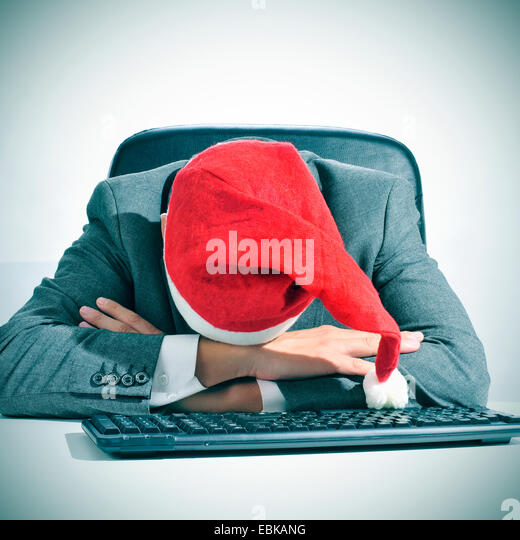 a man in suit with a santa hat sleeping in his desk after an office christmas party - Stock Image