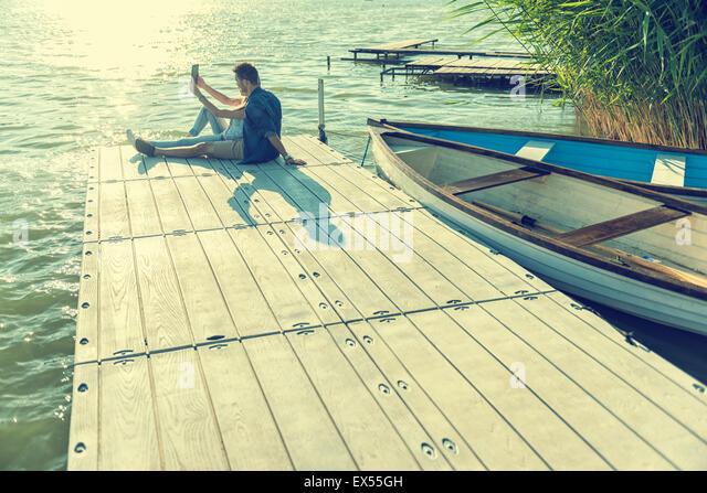 Couple in love sitting on the pier, selfie - Stock-Bilder