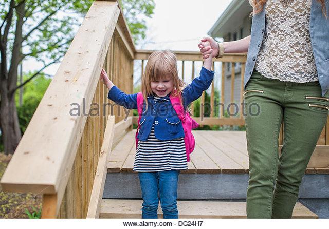 Mother helping daughter down wooden steps - Stock-Bilder