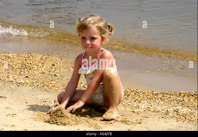 Young girl playing on beach - Stock Image