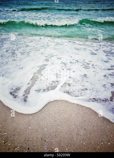 Ocean wave breaking at sandy shore at st. Pete's beach on the Gulf of Mexico Florida - Stock-Bilder