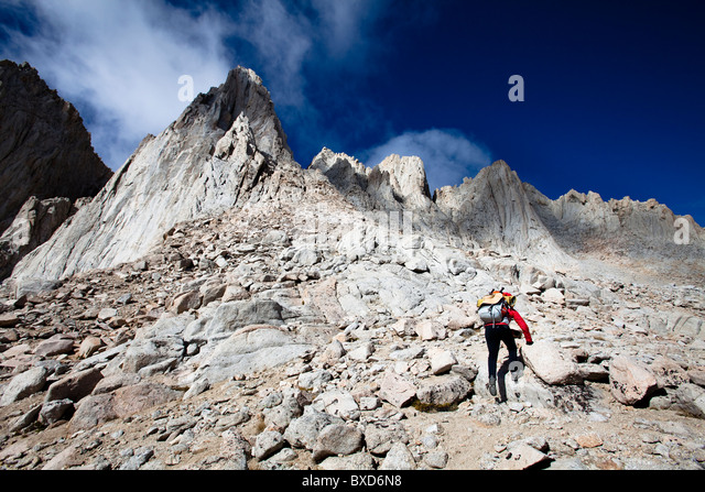 A female hiker scrambles up the mountaineer's route of Mount Whitney, California. - Stock Image