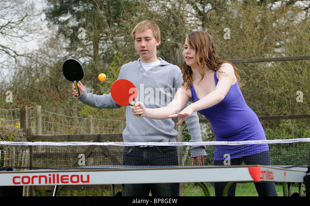 Young teenagers boy and girl playing table tennis - Stock Image