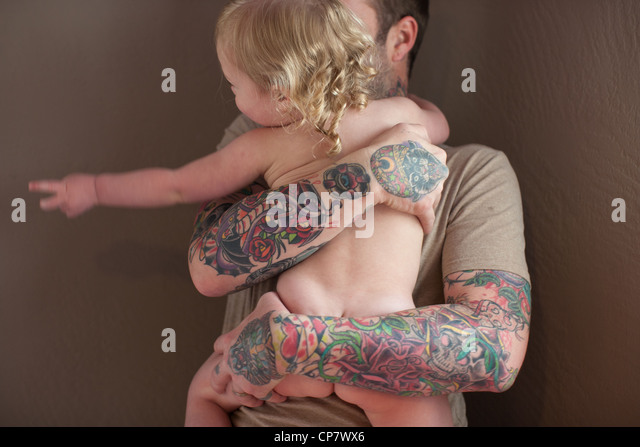 Father with tattoo on arm holds his baby girl. - Stock Image