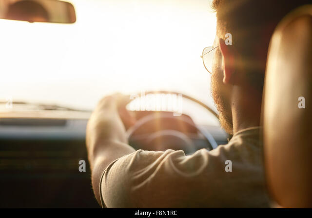 Close up shot of young man driving car. Rear view of man on road trip on a summer day, with sun flare. - Stock Image