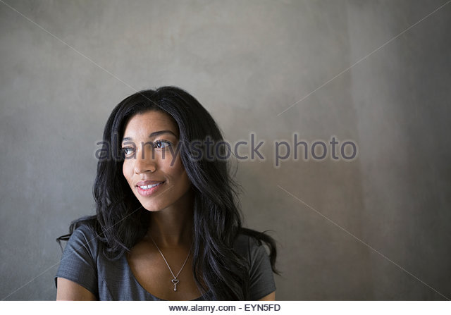 Pensive businesswoman with black hair looking away - Stock Image