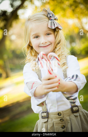 Cute Little Girl with a Bow in Her Hair Holding Her Christmas Candy Canes Outdoors. - Stock-Bilder