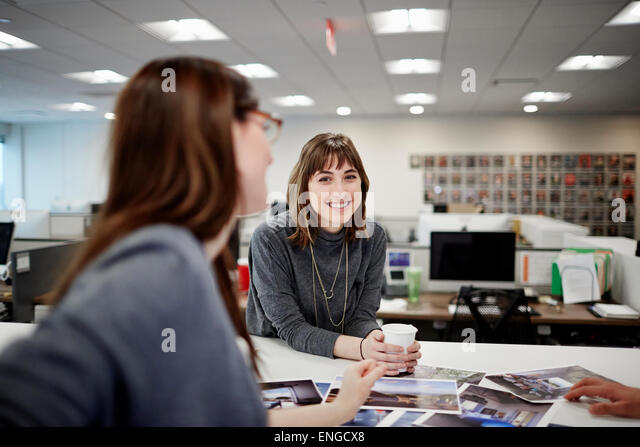 Two women seated in an office talking and laughing. - Stock Image