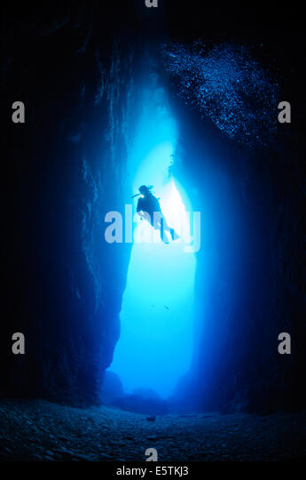 young female diver silhouetted against a blue sea in the inland sea cavern in Gozo, Malta - Stock Image