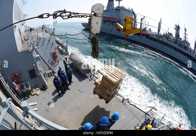 Sailors aboard the Arleigh Burke-class guided-missile destroyer USS McCampbell (DDG 85) receive supplies from the - Stock Image
