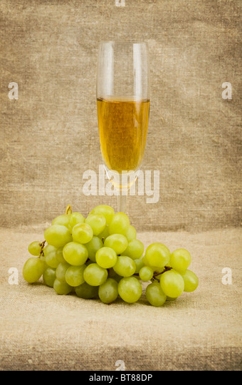 Goblet and green grape on sacking background - Stock Image