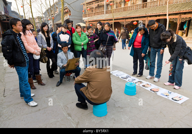Crowd watching street artist making a pencil sketch of a man in Huanglongxi, near Chengdu, Sichuan Province, China. - Stock Image