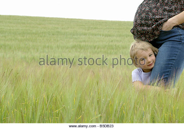 Pregnant woman and a child in a wheat field - Stock Image