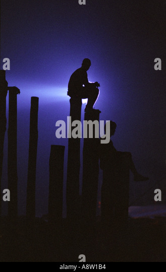 A lone concert goer watches a performance sitting alone on a pole with bright light shining behind him Woodstock - Stock Image