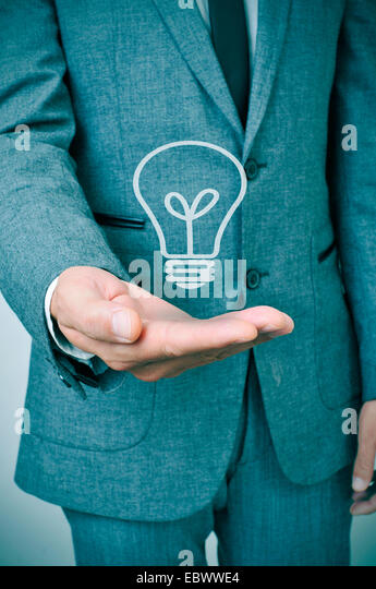 a man wearing a suit with a lightbulb drawn in his hand - Stock Image