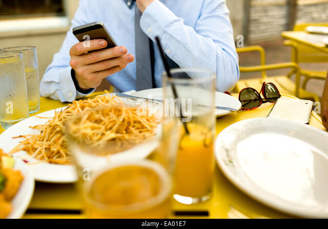 Cropped shot of young man texting on smartphone at sidewalk cafe - Stock-Bilder