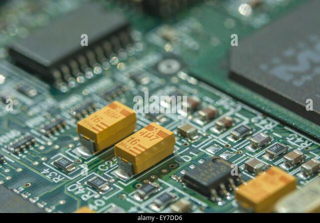 Macro-photo of printed circuit board (PCB) showing yellow tantalum (rare element) oxide capacitors. - Stock Image