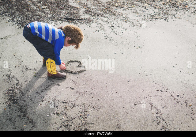 Boy in cowboy boots and raccoon hat drawing a heart in the sand - Stock-Bilder