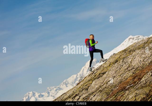 A runner runs up a steep mountain rock face at high altitude. - Stock-Bilder