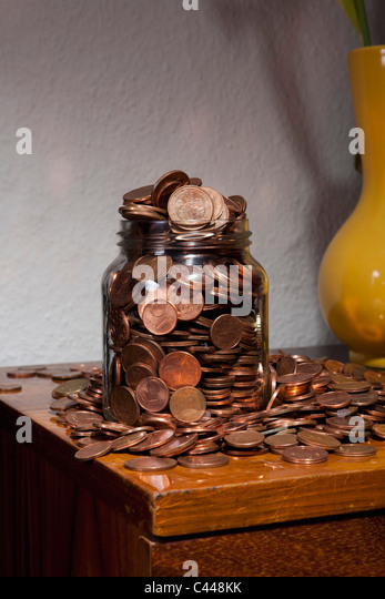 A jar overflowing with European Union coins - Stock Image