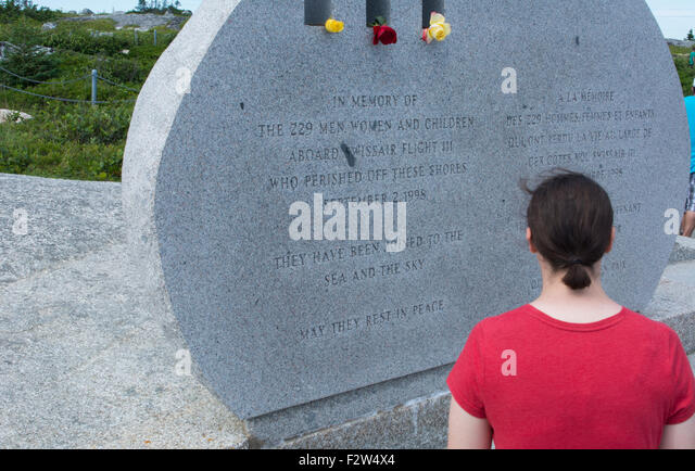 Canada Peggy's Cove Nova Scotia memorial for tragedy of SwissAir 111 flight  with 229 dead with woman honoring - Stock Image